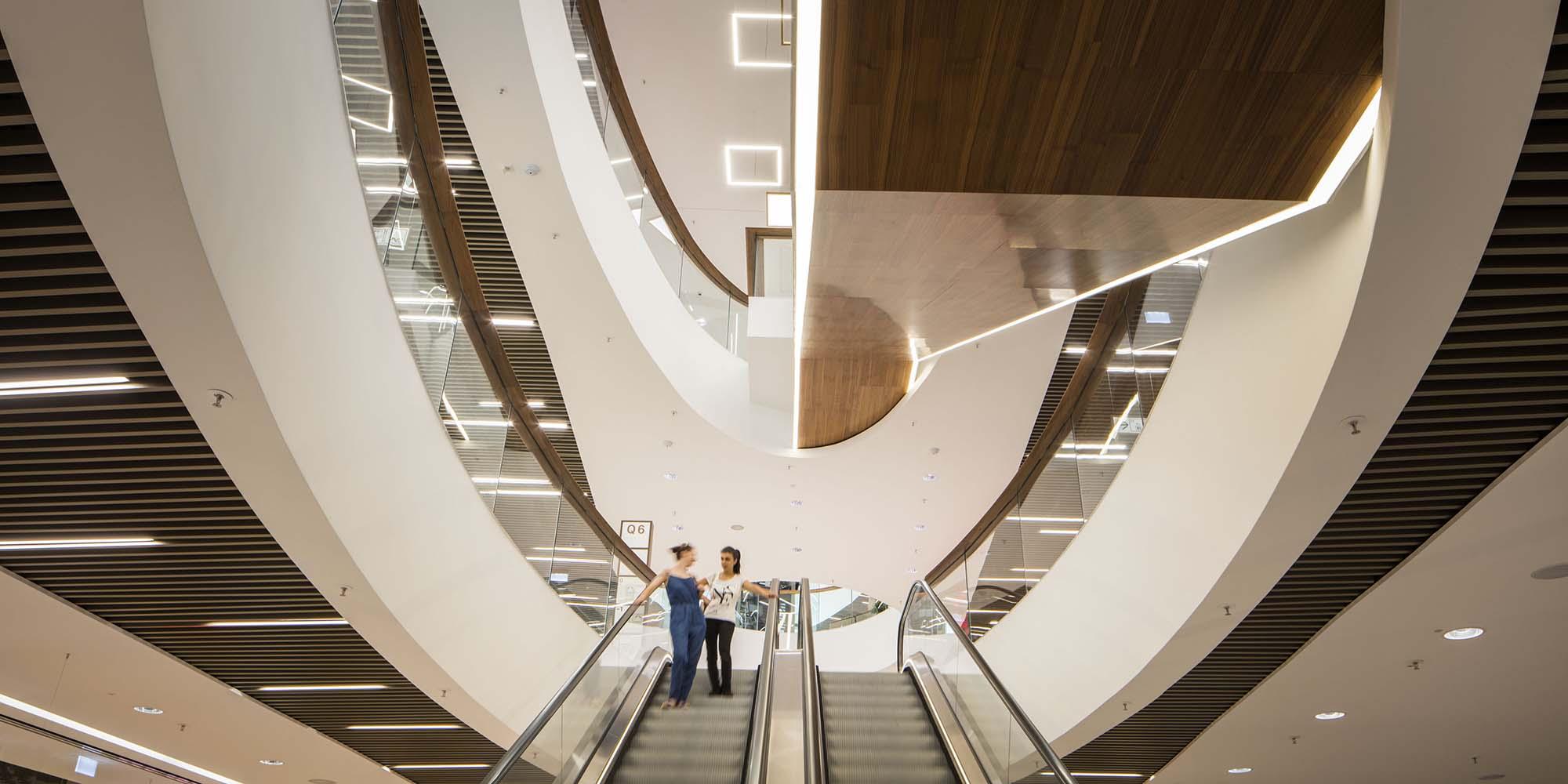 Architekturfoto: Retail - Blick auf eine Rolltreppe in shopping-mall mit zwei Kundinnen. Q6Q7 Mannheim