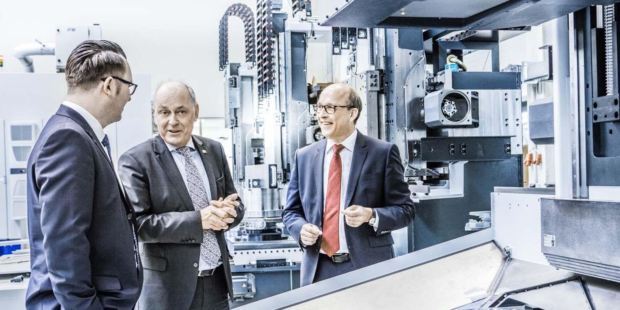 Business Portrait von drei Personen im Gespräch. Sie stehen zwischen industriellen Anlagen. Moderne Industriefotografie