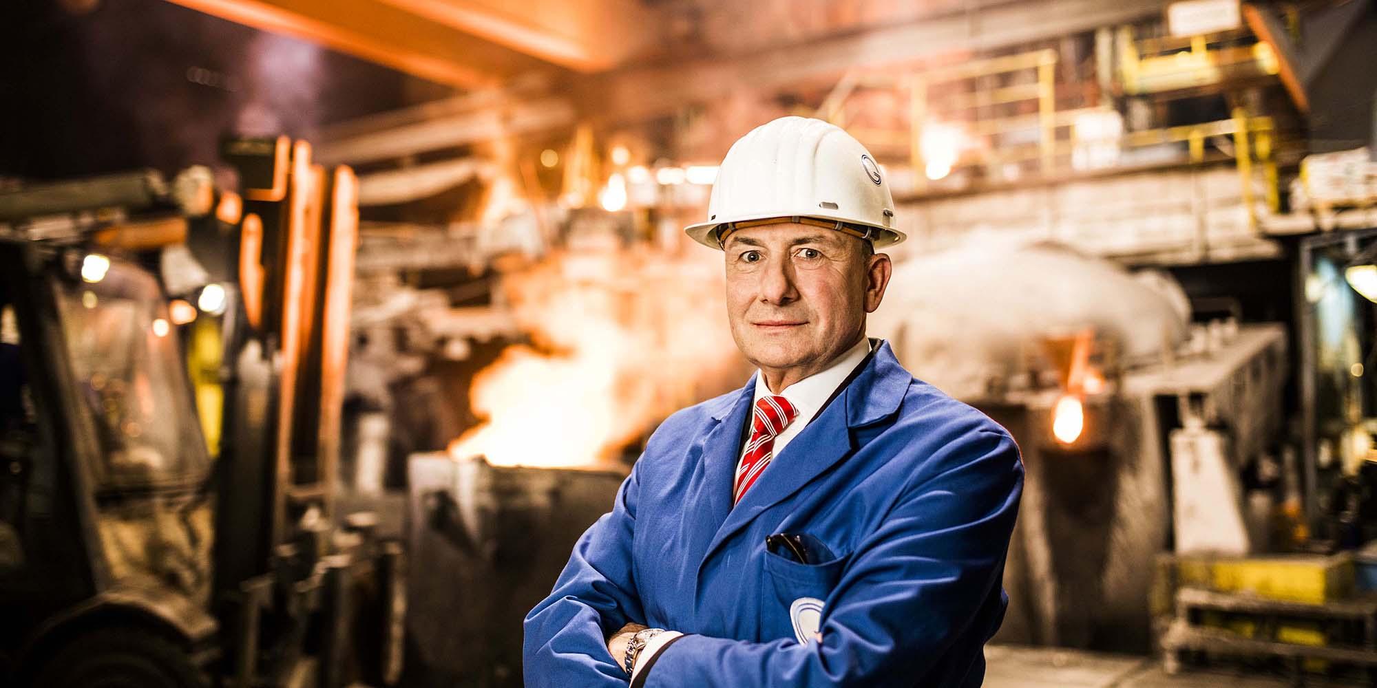 Business Portrait Hans-Jürgen Brenninger. Der Geschäftsführer der Gienanth GmbH steht mit Helm und Blaumann in der Giesereihalle.