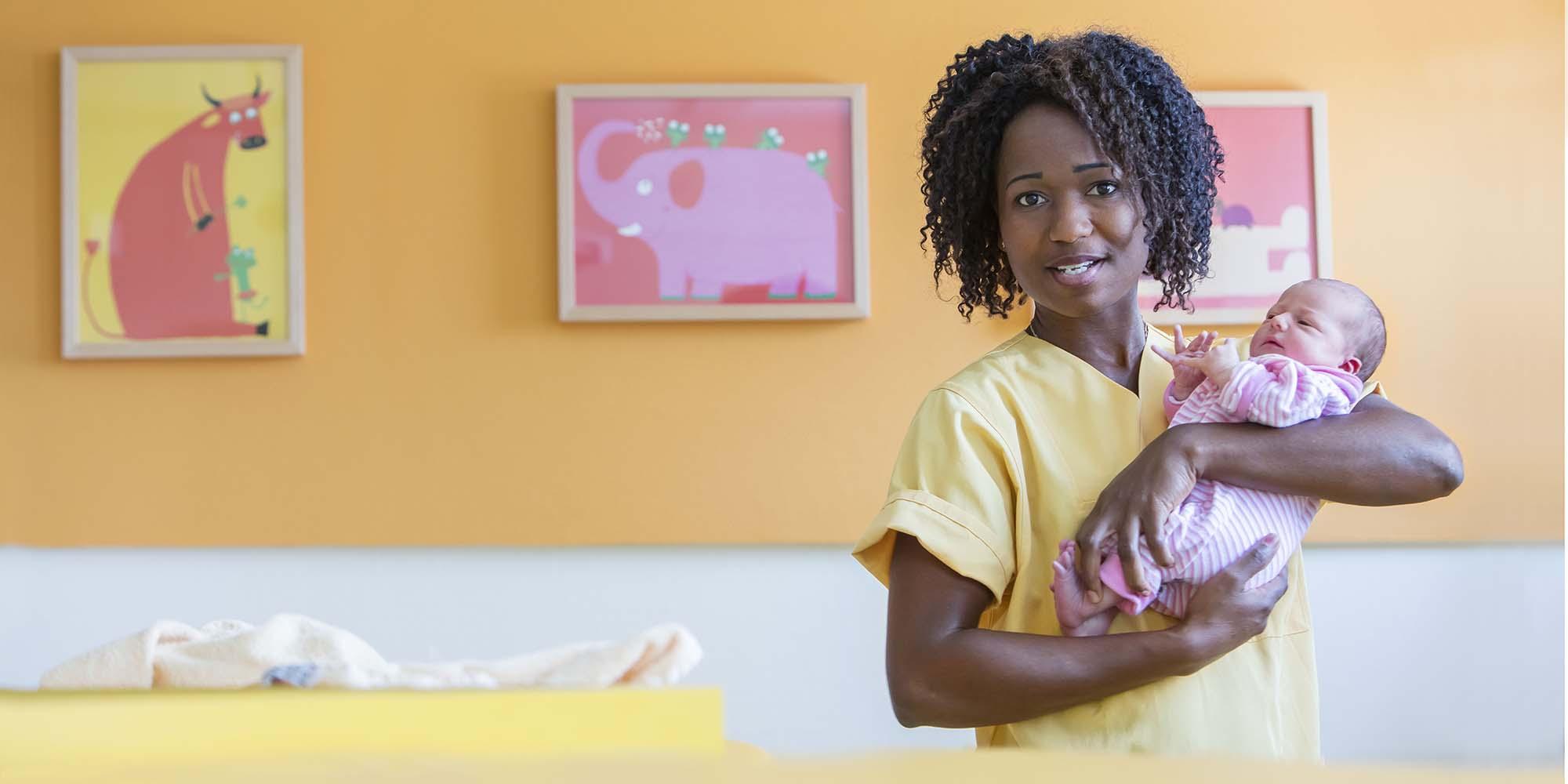 healthcare fotografie: eine afrodeutsche Hebamme hält liebevoll ein neugeborenes Mädchen.