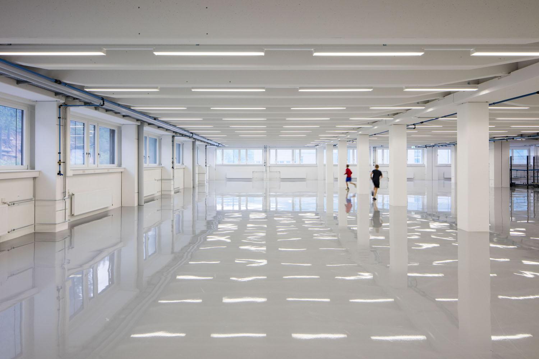 Innenaufnahme einer sanierten Gewerbehalle. Zwei Jungs rennen durch die leere Halle.