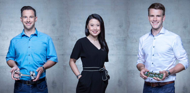 Business-Portrait von drei Mitarbeitern der Firma Mahle vor Betonwand. Halbfigur.