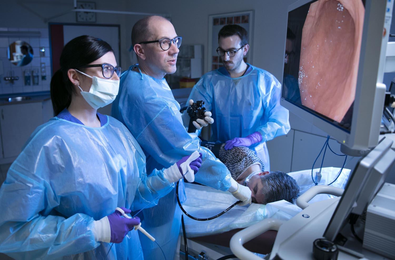 Healthcare Fotografie: EIne Gastroskopie wird von zwei Ärzten und einer Krankenschwester durchgeführt.