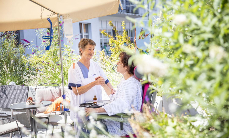 Healthcare Fotografie: Eine schwerkranke Patientin sitzt im Pflegestuhl im Hospitzgarten der GRN-Klink. Eine Krankenschwester steht bei ihr und massiert der Patientin den Arm.