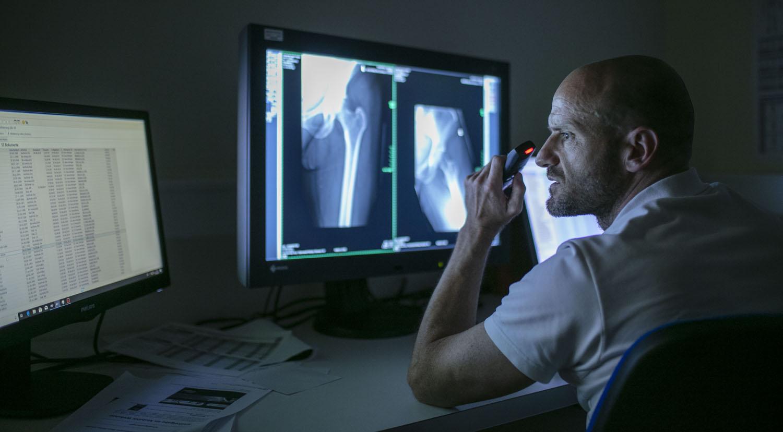 Healthcare Fotografie: Ein Radiologe analysiert Röntgenaufnahmen am Monitor. Den Befund spricht er in ein Diktiergerät. Der Raum ist abgedunkelt : low-key-Fotografie.