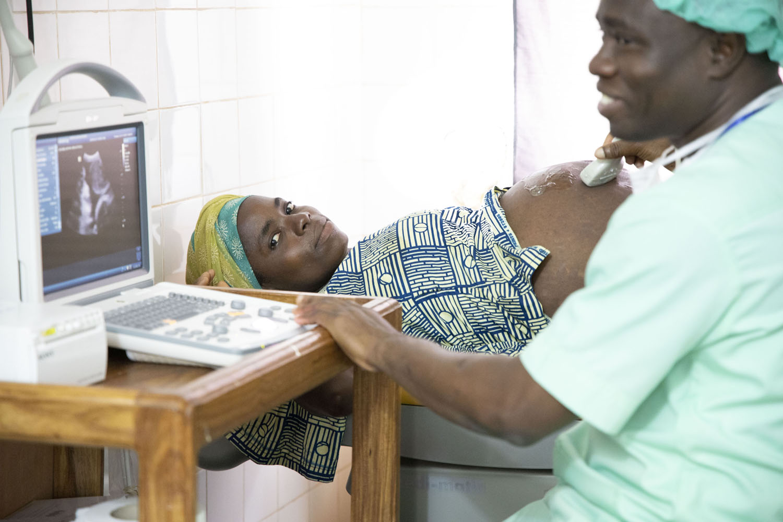 Healthcare Fotografie: In einem afrikanischen Krankenhaus untersucht ein Arzt eine schwangere junge Patientin.