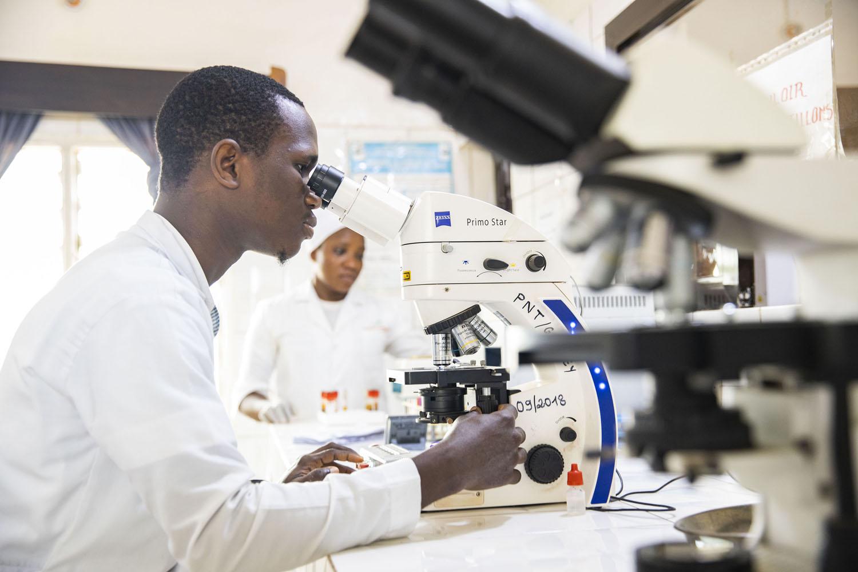 Healthcare Fotografie: Labor-Mitarbeiter im afrikanischen Krankenhaus untersucht ein Präparat unter dem Mikroskop
