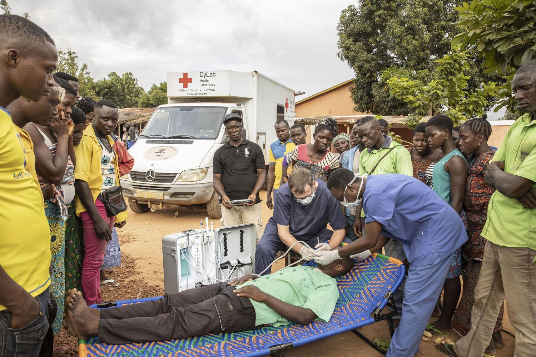 Healthcare Fotografie: ein Zahnazt hat im afrikanischen Dorf eine mobile Behandlungseinheit aufgebaut. Er behandelt einen Patienten auf dem Dorfplatz. Viele Dorfbewohner beobachten die Szene.