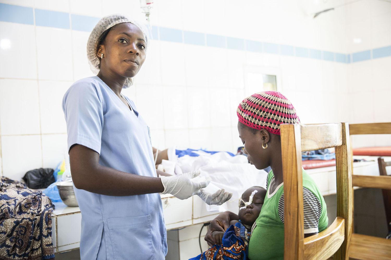 Healthcare Fotografie: in der Notaufnahme eines afrikanischen Krankrenhauses verabreicht eine Krankenschwester einem kleinen Kind Nahrung über die Magensonde.