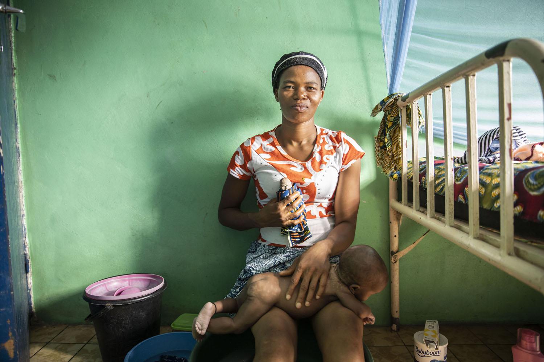 Healthcare Fotografie: Kinderstation eines afrikanischen Krankenhauses. Eine junge Mutter wäscht ihren Säugling. In der Hand hält sie eine Puppe, die nach Voodoo-Tradion das gestorbene Zwillingskind repräsentiert.