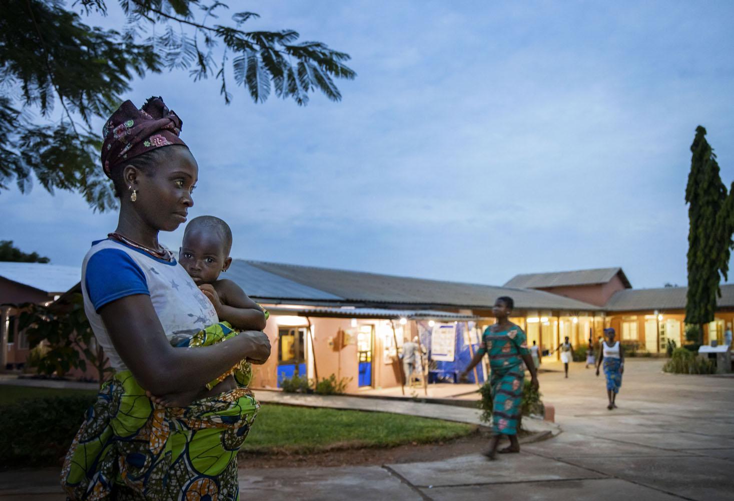 Healthcare Fotografie: eine afrikanische junge Mutter mit Baby auf dem Arm kommt abends im Krankenhaus in Gohomey, Benin an. Dämmerungsaufnahme mit beleutetem Krankenhaus und einigen Patienten im Hintergrund.