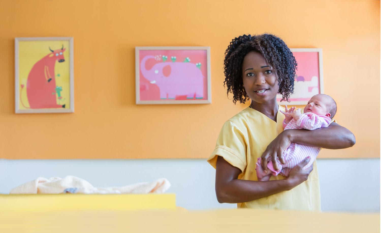 inszeniertes Portrait afrodeutsche Hebamme mit Baby
